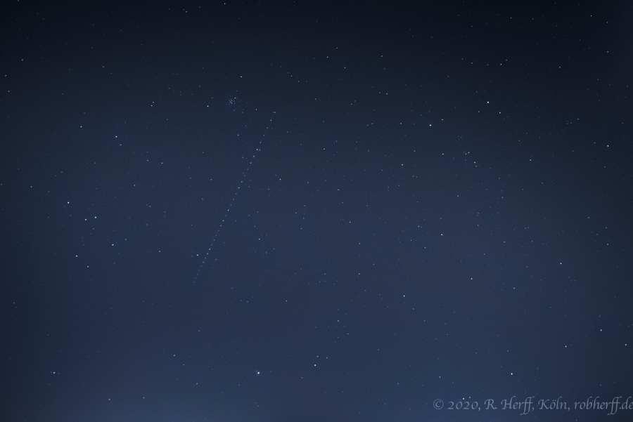 Nachthimmel mit Starlink-Kette im Sternbild Krebs